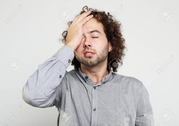 lifestyle, health and people concept: Close up of frustrated young man with head in hand